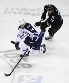 Winnipeg defenceman Zach Bogosian (44) is chased by San Jose centre Joe Thornton during first-period action Thursday night.