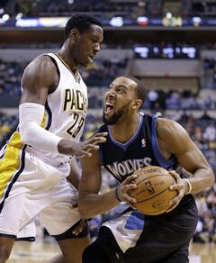 Minnesota Timberwolves forward Derrick Williams, right, crashes into Indiana Pacers center Ian Mahinmi while driving the baseline in the first half of an NBA basketball game in Indianapolis, Wednesday, March 13, 2013. (AP Photo/Michael Conroy)