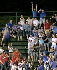 A Chicago Cubs' baseball fan catches Anthony Rizzo's home run off Cincinnati Reds starting pitcher Alfredo Simon in the left field bleachers during the sixth inning of a baseball game Monday, June 23, 2014, in Chicago. (AP Photo/Charles Rex Arbogast)