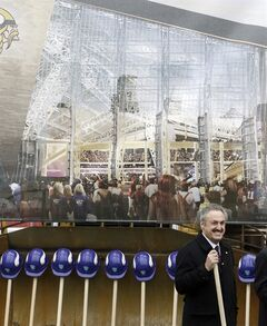 FILE - In this Dec. 3, 2013, file photo, a large rendering of the new Minnesota Vikings stadium hangs behind Vikings owner Zygi Wilf, right, as he waits to shovel the first dirt during one of several ceremonial dirt tosses at a groundbreaking ceremony for the Vikings new NFL football stadium in Minneapolis. Minneapolis has been awarded the 2018 Super Bowl by NFL owners. The owners rewarded the Vikings for arranging to build a new stadium on the site of the old Metrodome by choosing Minneapolis over New Orleans and Indianapolis.(AP Photo/Jim Mone, File)