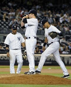 New York Yankees third baseman Yangervis Solarte, left, and shortstop Derek Jeter, right, join pitcher David Phelps on the mound as he reacts after Seattle Mariners' Brad Miller hit a two-run single in the seventh inning of a baseball game at Yankee Stadium on Monday, June 2, 2014, in New York. (AP Photo/Kathy Kmonicek)