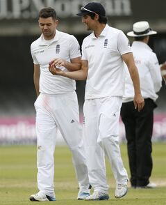England's captain Alastair Cook, right, talks to bowler James Anderson on the fifth day of the first Test cricket match between England and Sri Lanka at Lord's cricket ground in London, Monday June 16, 2014. (AP Photo/Alastair Grant)