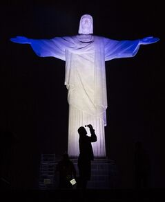 A man takes a photo of Christ the Redeemer statue as it is lit with the colors of the 32 national teams that will take part on the World Cup, in Rio de Janeiro, Brazil, Wednesday, June 11, 2014. The World Cup soccer tournament starts Thursday with Brazil facing Croatia in the opening match. (AP Photo/Leo Correa)