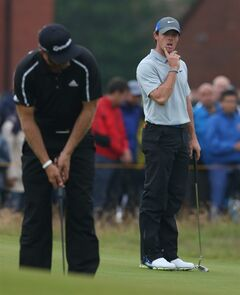 Rory McIlroy of Northern Ireland, right, watches Dustin Johnson of the US putt on the 2nd green during the third day of the British Open Golf championship at the Royal Liverpool golf club, Hoylake, England, Saturday July 19, 2014. (AP Photo/Jon Super)