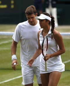Max Mirnyi of Belarus, left, and Hao-Ching Chan of Taiwan talk between points during their mixed doubles final against Nenad Zimonjic of Serbia and Samantha Stosur of Australia at the All England Lawn Tennis Championships in Wimbledon, London, Sunday July 6, 2014. (AP Photo/Pavel Golovkin)