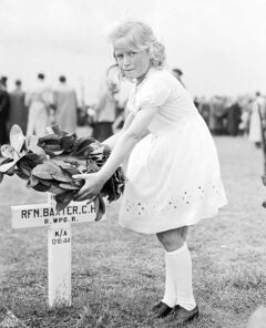 A year after the war's end, a Dutch girl tends to the grave of a  Winnipeg soldier killed in the  Netherlands.