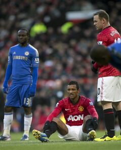Manchester United's Nani sits injured on the pitch before being substituted during his team's English FA Cup quarterfinal soccer match against Chelsea at Old Trafford Stadium, Manchester, England, Sunday March 10, 2013. (AP Photo/Jon Super)