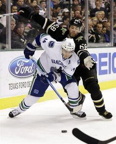 Dallas Stars right wing Jaromir Jagr (68), of the Czech Republic, pressures Vancouver Canucks center Alex Burrows (14) as Burrows attempts to clear the puck from behind the net during the first period of an NHL hockey game, Thursday, Feb. 21, 2013, in Dallas. (AP Photo/Tony Gutierrez)