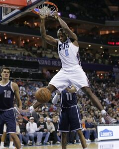 Charlotte Bobcats' Bismack Biyombo (0) dunks as Oklahoma City Thunder's Steven Adams (12) and Jeremy Lamb (11) watch during the first half of an NBA basketball game in Charlotte, N.C., Friday, Dec. 27, 2013. (AP Photo/Chuck Burton)