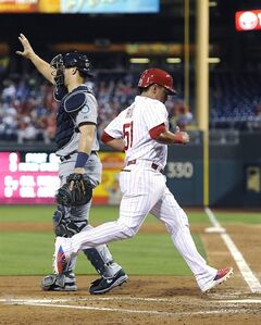 Philadelphia Phillies' Carlos Ruiz (51) scores a run from a Marlon Byrd double while Seattle Mariners catcher Mike Zunino signals to the infield during the third inning of an interleague baseball game on Monday, Aug. 18, 2014, in Philadelphia. (AP Photo/Michael Perez)