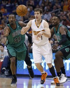 Phoenix Suns' Goran Dragic (1), of Slovenia, slips through the defense of Boston Celtics' Gerald Wallace (45) and Jeff Green to get a pass off to a teammate during the second half of an NBA basketball game, Wednesday, Feb. 19, 2014, in Phoenix. The Suns defeated the Celtics 100-94. (AP Photo/Ross D. Franklin)