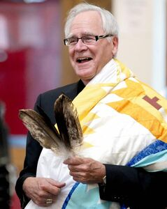 Archbishop James Weisgerber reacts to a joke made by Wab Kinew, who conducted a ceremony at the Thunderbird House. Anishinaabe elders and community leaders Tobasonakwut Kinew, Fred Kelly, Phil Fontaine and Bert Fontaine adopted the archbishop in a traditional Naabagoondiwin adoption ceremony.