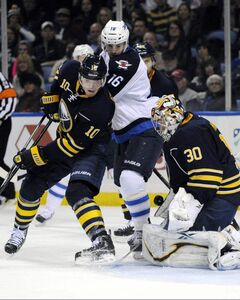 Buffalo Sabres defenceman Christian Ehrhoff (left) battles with Winnipeg Jets left-winger Andrew Ladd as Sabres goaltender Ryan Miller makes a save during the second period of an NHL hockey game in Buffalo, N.Y., Tuesday.