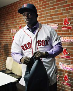 Rusney Castillo leaves the table after speaking with reporters during a news confernce after the baseball game between the Boston Red Sox and the Seattle Mariners in Boston, Saturday, Aug. 23, 2014. The Red Sox announced during the game that they signed Castillo, a Cuban defector, to a seven-year contract, beginning in 2014. (AP Photo/Michael Dwyer)