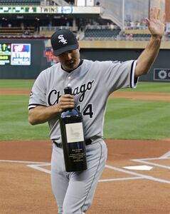 Chicago White Sox's Paul Konerko acknowledges the crowd after he was presented a large bottle of wine by Minnnesota Twins' Joe Mauer and Glen Perkins prior to a baseball game, Wednesday, Sept. 3, 2014, in Minneapolis. It was part of honoring Konerko in his farewell baseball season. (AP Photo/Jim Mone)