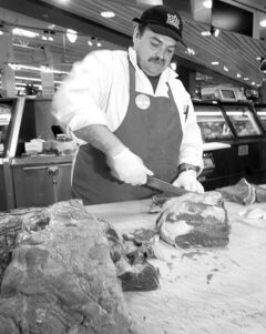 Butcher Bob Corbeil prepares beef at the Whole Foods Market in West Vancouver.