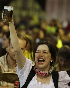 A Brazilian of German descent cheers for Germany as she watches the World Cup semifinal match between Brazil and Germany on a screen in Blumenau, Brazil, Tuesday, July 8, 2014. The German community in southern Brazil organized an Oktoberfest party to celebrate the Brazil vs. Germany match. (AP Photo/Nelson Antoine)