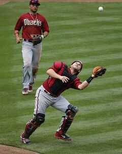 Arizona Diamondbacks catcher Miguel Montero catches a pop-up as teammate Martin Prado watches, against the Chicago Cubs during the third inning of a spring training baseball game, Thursday, Feb. 27, 2014, in Mesa, Ariz. (AP Photo/Matt York)