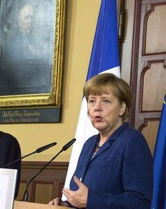 German chancellor Angela Merkel gestures during a news conference with French President Hollande at the town hall in Stralsund, northern Germany, Saturday, May 10, 2014 during the second day of Hollande's two days visit to Merkel's scenic home constituency on the Baltic coast . One of the main talking points is expected to be over whether the European Union should impose further sanctions on Russia, for its involvement in the Ukraine crisis. (AP Photo/Gero Breloer)