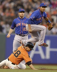 New York Mets shortstop Ruben Tejada hops over San Francisco Giants' Buster Posey, bottom, after completing a double play in the fourth inning of a baseball game Friday, June 6, 2014, in San Francisco. Giants' Michael Morse was out at first base. At left, Mets second baseman Daniel Murphy backs up the play. (AP Photo/Ben Margot)
