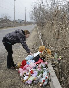 Shannon Whetstone reads notes left at the scene where six teens died early Sunday in Warren, Ohio, on Monday, March 11, 2013. Two teens who escaped a crash that killed six friends in a swampy pond wriggled out of the wreckage by smashing a rear window and swimming away from the SUV, a state trooper said Monday. (AP Photo/Tony Dejak)