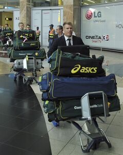 Australia's cricket player David Warner, front, with teammates pushes trolleys with their bags during their arrival at OR Tambo International Airport in Johannesburg, South Africa, Wednesday, Jan. 29, 2013, for their Test cricket tour against South Africa. (AP Photo/ Themba Hadebe)