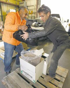 Hussain Guisti (left) and Ramin Javadi prepare food to be shipped north.