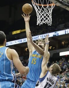 New Orleans Hornets' Robin Lopez goes in for a layup over Minnesota Timberwolves' Luke Ridnour, right, in the first half on an NBA basketball game Sunday, March 17, 2013, in Minneapolis. (AP Photo/Jim Mone)