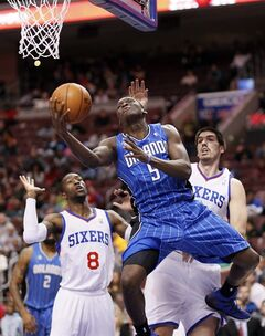 Orlando Magic's Victor Oladipo, center, drives in for a layup between Philadelphia 76ers' Tony Wroten, left, and Byron Mullens, right, during the first half of an NBA basketball game on Wednesday, Feb 26, 2014, in Philadelphia. (AP Photo/Tom Mihalek)