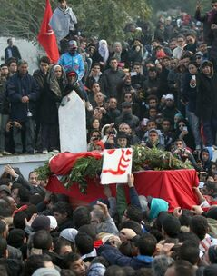 The coffin, wrapped in the Tunisian red flag, of slain opposition leader Chokri Belaid is carried at el Jallez cemetery while thousands attend his funerals near Tunis, Friday Feb. 8, 2013. The Wednesday Feb. 6 assassination of prominent government critic Chokri Belaid plunged the country into one of its deepest political crises since the overthrow of the dictatorship in 2011.