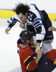 The Jets' Chris Thorburn (22) and the Panthers' Krys Barch fight in the second period on Friday in Sunrise, Fla.