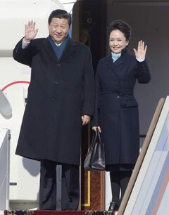 Chinese President Xi Jinping, left, and his wife Peng Liyuan wave upon their arrival to the government airport Vnukovo II, outside Moscow on March 22.