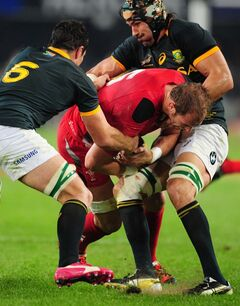 Wales' Alun-Wyn Jones, center, is tackled by South Africa's Francois Louw, left, and Victor Matfield, right, during their Rugby test match in Durban, South Africa, Saturday, June 14, 2014. (AP Photo)