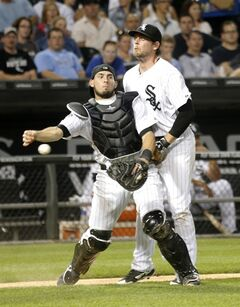 Chicago White Sox third baseman Conor Gillaspie, right, runs into catcher Adrian Nieto after Nieto fielded a bunt by Kansas City Royals' Alcides Escobar during the sixth inning of a baseball game Tuesday, July 22, 2014, in Chicago. Escobar was safe at first. (AP Photo/Charles Rex Arbogast)