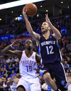 Memphis Grizzlies guard Nick Calathes (12) goes to the basket in front of Oklahoma City Thunder guard Reggie Jackson (15) during the first quarter of an NBA basketball game on Monday, Feb. 3, 2014, in Oklahoma City. (AP Photo/Alonzo Adams)
