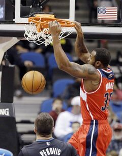 Washington Wizards' Trevor Booker dunks during the first quarter of an NBA basketball game as Minnesota Timberwolves' Nikola Pekovic of Montenegro, watches on Friday, Dec. 27, 2013, in Minneapolis. (AP Photo/Jim Mone)