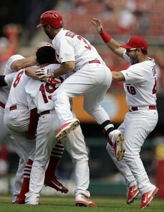 St. Louis Cardinals' Peter Bourjos (8) is congratulated by teammates after hitting a walkoff-single to score Yadier Molina during the ninth inning of a baseball game against the Pittsburgh Pirates, Wednesday, Sept. 3, 2014, in St. Louis. The Cardinals won 1-0. (AP Photo/Jeff Roberson)
