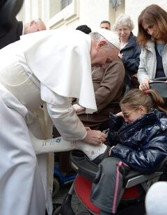 Pope Francis signs a plaster cast for a girl Wednesday in St. Peter;s Square.