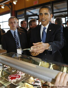 President Barack Obama tries to pay for some Canadian Maple Leaf cookies -- seen in the display case below -- as he makes an unannounced visit to a market in Ottawa on Thursday.