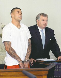 Aaron Hernandez (left) stands with his attorney Michael Fee  during Wednesday's arraignment in Attleboro District Court.