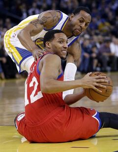 Philadelphia 76ers' Evan Turner (12) looks to pass after picking up up a loose ball next to Golden State Warriors' Andre Iguodala during the first half of an NBA basketball game, Monday, Feb. 10, 2014, in Oakland, Calif. (AP Photo/Marcio Jose Sanchez)