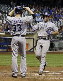 Colorado Rockies' Ryan Wheeler is congratulated at home by Justin Morneau (33) after hitting a grand slam during the fourth inning of a baseball game against the Milwaukee Brewers Thursday, June 26, 2014, in Milwaukee. (AP Photo/Morry Gash)