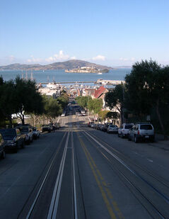 Straight down Hyde Street are Fisherman's Wharf and Alcatraz, as seen from the deck of a cable car in San Francisco. Some streets here have slopes of up to 30 degrees.