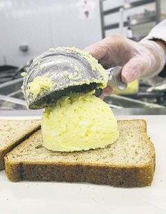 Egg salad sandwiches are prepared  on an assembly line.