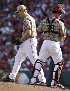 Cincinnati Reds starting pitcher Homer Bailey talks with catcher Devin Mesoraco in the eighth inning of a baseball game against the Milwaukee Brewers, Saturday, July 5, 2014, in Cincinnati. Bailey was the losing pitcher in the game won by Milwaukee 1-0. (AP Photo/Al Behrman)