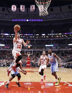 Chicago Bulls guard Kirk Hinrich (12) scores past Denver Nuggets guard Randy Foye as Joakim Noah (13) and Denver Nuggets forward Kenneth Faried (35) watch during the first half of an NBA basketball game Friday, Feb. 21, 2014, in Chicago. (AP Photo/Charles Rex Arbogast)