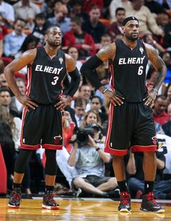 Miami Heat's Dwyane Wade (3) and LeBron James (6) stand together during the second quarter of an NBA basketball game against the Orlando Magic in Miami on Wednesday, March 6, 2013. (AP Photo/El Nuevo Herald, David Santiago)