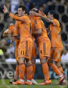 Real Madrid Gareth Bale, left, celebrates a goal with his teammates against Espanyol during a Copa del Rey soccer match at Cornella-El Prat stadium in Cornella Llobregat , Spain, Tuesday, Jan. 21, 2014. (AP Photo/Manu Fernandez)