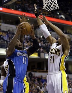 Orlando Magic forward Glen Davis, left, looks to shoot under Indiana Pacers forward David West in the first half of an NBA basketball game in Indianapolis, Monday, Feb. 3, 2014. (AP Photo/Michael Conroy)