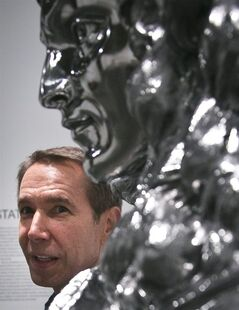 Jeff Koons pose next to his sculpture